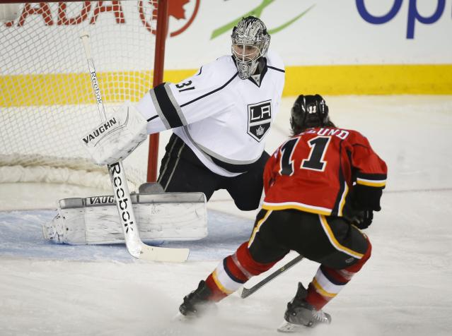 Los Angeles Kings goalie Martin Jones, left, gets pressured by Calgary Flames' Mikael Backlund, from Sweden, during second period NHL hockey action in Calgary, Alberta, Monday, March 10, 2014. (AP Photo/The Canadian Press, Jeff McIntosh)