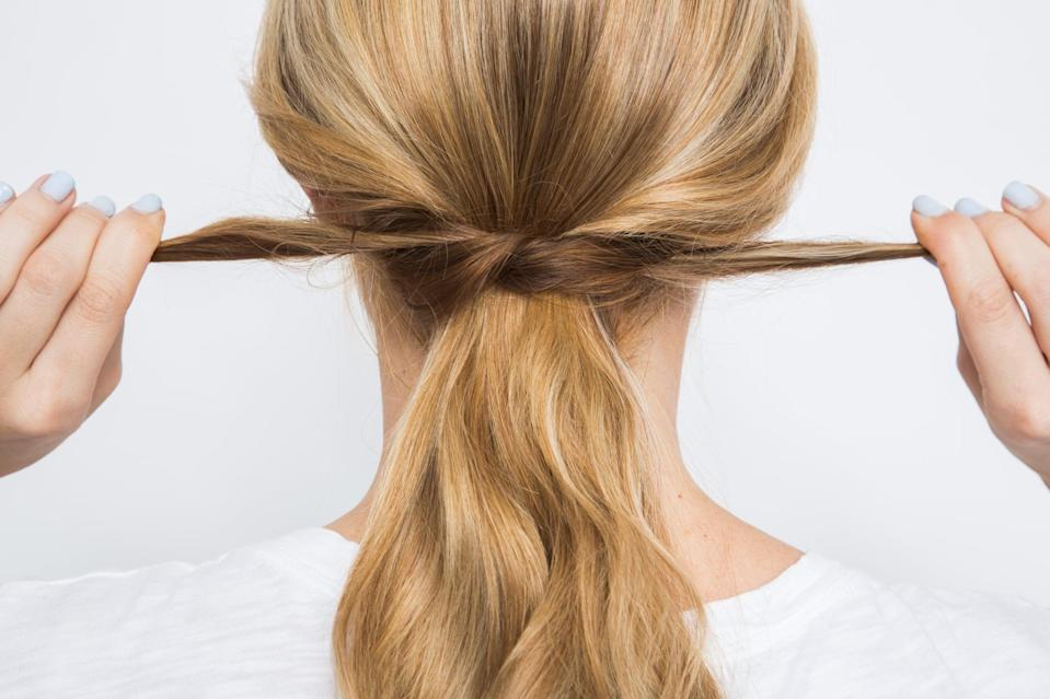 <p>Gather two small sections of hair right behind the ears and knot them around your ponytail. Stick in one bobby pin at the base to keep the style from unraveling. Then, when you're ready to rock your waves again, you can easily loosen the knot.</p>