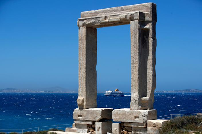 A ferry on the water in Greece and an ancient marble gate.