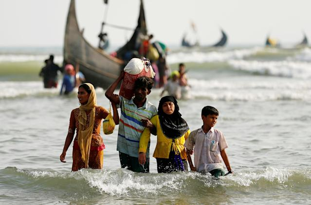 <p>Rohingya refugees walk to the shore with his belongings after crossing the Bangladesh-Myanmar border by boat through the Bay of Bengal in Teknaf, Bangladesh, Sept. 5, 2017. (Photo: Mohammad Ponir Hossain/Reuters) </p>