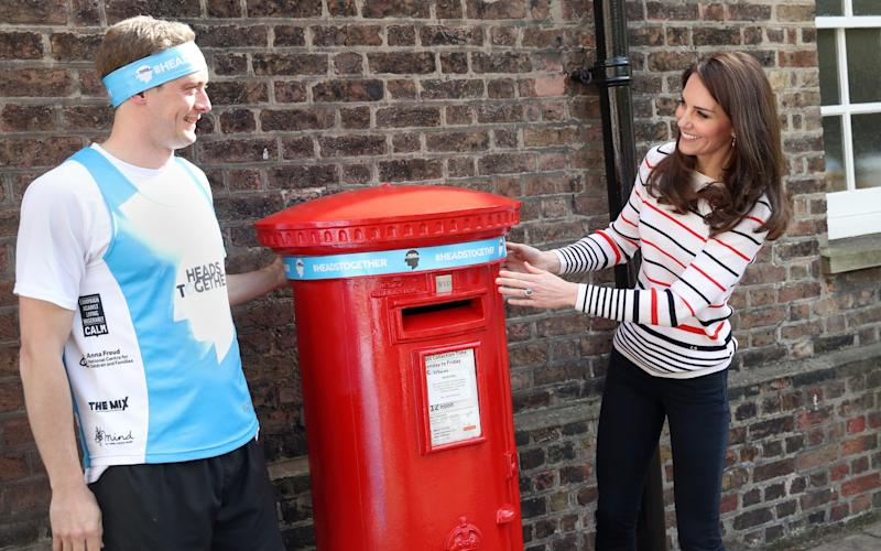 The Duchess of Cambridge, with runner Alex Stanley, put a Heads Together headband onto the Kensington Palace post-box - Credit: Getty