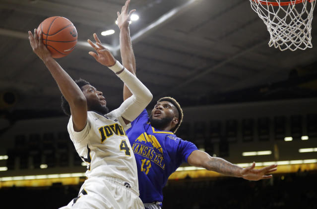 Iowa guard Isaiah Moss, left, drives to the basket over UKMC forward Jamel Allen during the first half of an NCAA college basketball game, Thursday, Nov. 8, 2018, in Iowa City, Iowa.(AP Photo/Charlie Neibergall)