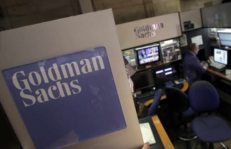 FILE - In a March 15, 2012 file photo, a trader works in the Goldman Sachs booth on the floor of the New York Stock Exchange.  The Justice Department on Thursday, Aug. 9, 2012 said it won't prosecute Goldman Sachs or its employees in a financial fraud probe. (AP Photo/Richard Drew, File)