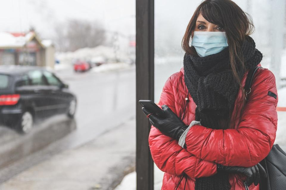 Woman waiting for the bus, wearing protective mask to protect from covid-19