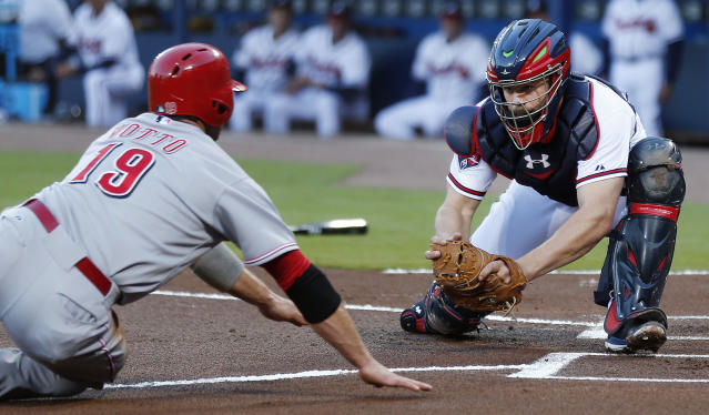 Cincinnati Reds first baseman Joey Votto (19) is tagged out by Atlanta Braves catcher Evan Gattis (24) as he tries to score on a fly ball in the first inning of a baseball game Friday, April , 25, 2014 in Atlanta. (AP Photo/John Bazemore)