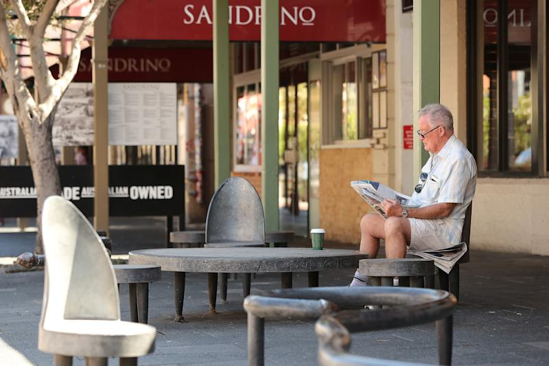 A man reads a local newspaper while sitting on roadside seating on South Terrace on March 26, 2020 as local newspaper cut in major News Corp cull
