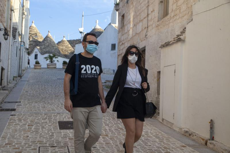 ALBEROBELLO, ITALY - MAY 24: A couple of engaged couples with a mask stroll together in the historic center of the Trulli on May 24, 2020 in Alberobello, Italy. Restaurants, bars, cafes, hairdressers and other shops have reopened, subject to social distancing measures, after more than two months of a nationwide lockdown meant to curb the spread of Covid-19. (Photo by Donato Fasano/Getty Images)