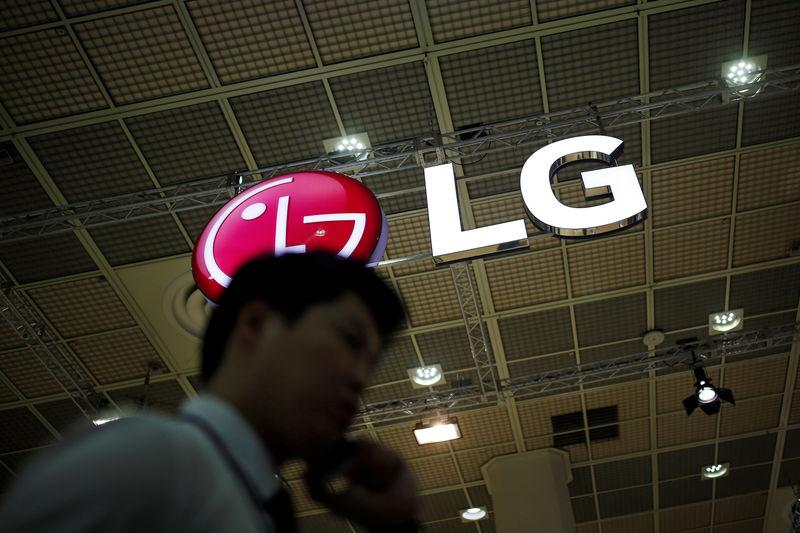 A man talking on his phone walks past the logo of LG Electronics during Korea Electronics Show 2016 in Seoul