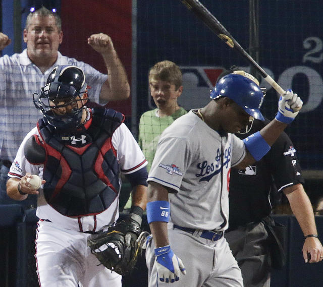 Los Angeles Dodgers' Juan Uribe, right, walks off the plate after striking out in the eighth inning against the Atlanta Braves during Game 2 of the National League division series on Friday, Oct. 4, 2013, in Atlanta. (AP Photo/Dave Martin)