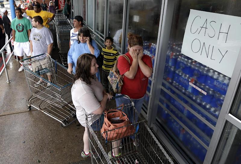 Ashley Clague, right, holds her face as she waits with Jean Fernandez, left, to buy groceries after Hurricane Isaac in Chalmette, La.,Thursday, Aug. 30, 2012. Isaac's maximum sustained winds had decreased to 45 mph and the National Hurricane Center said it was expected to become a tropical depression by Thursday night. The storm's center was on track to cross Arkansas on Friday and southern Missouri on Friday night, spreading rain as it goes. (AP Photo/David J. Phillip)