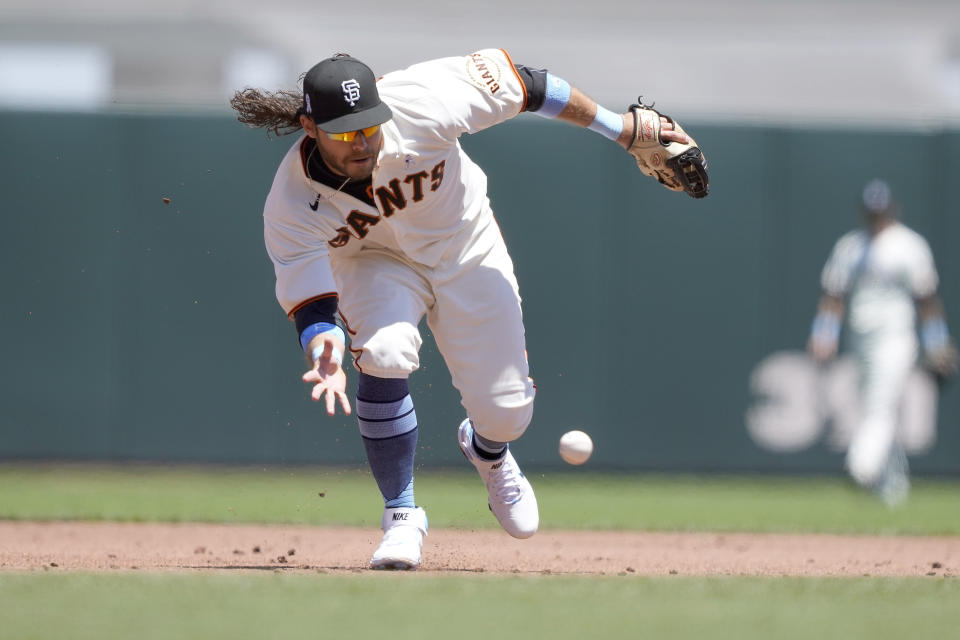 San Francisco Giants shortstop Brandon Crawford (35) barehands a ground ball hit by Philadelphia Phillies' Luke Williams during the third inning of a baseball game Sunday, June 20, 2021, in San Francisco. Williams was out at first base. (AP Photo/Tony Avelar)