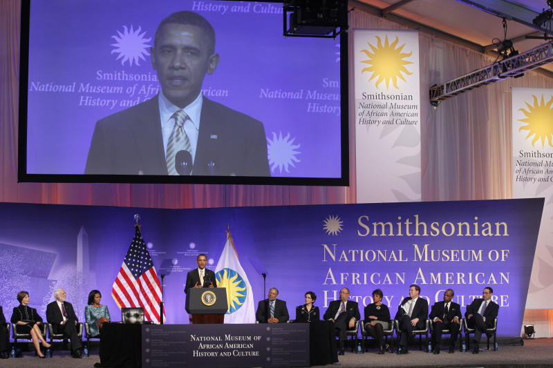 President Barack Obama speaks at the groundbreaking for the Smithsonian National Museum of African American History and Culture in Washington, Wednesday, Feb. 22, 2012. Pictured on stage, from left to right: former first lady Laura Bush; Wayne Clough, Secretary of the Smithsonian Institution; first lady Michelle Obama; Lonnie Bunch, Director of the National Museum of African American History and Culture; France Cordova, chair, Smithsonian Board of Regents; Richard Parsons, co-chair of the National Museum of African American History and Culture Council; Linda Johnson Rice, co-chair of the National Museum of African American History and Culture Council; Kansas Gov. Sam Brownback; Rev. Calvin Butts of Abyssinian Baptist Church in New York City; Washington Mayor Vincent Gray.  (AP Photo/Charles Dharapak)