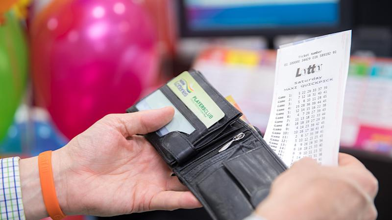 Pictured is a stock image of a man pulling a Lotto ticket out of his wallet. Source: The Lott