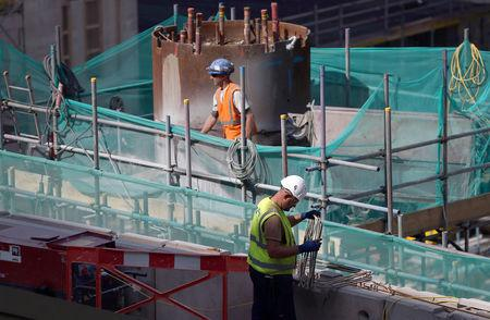 FILE PHOTO: Builders work on a construction site in London, Britain August 17, 2016. REUTERS/Neil Hall