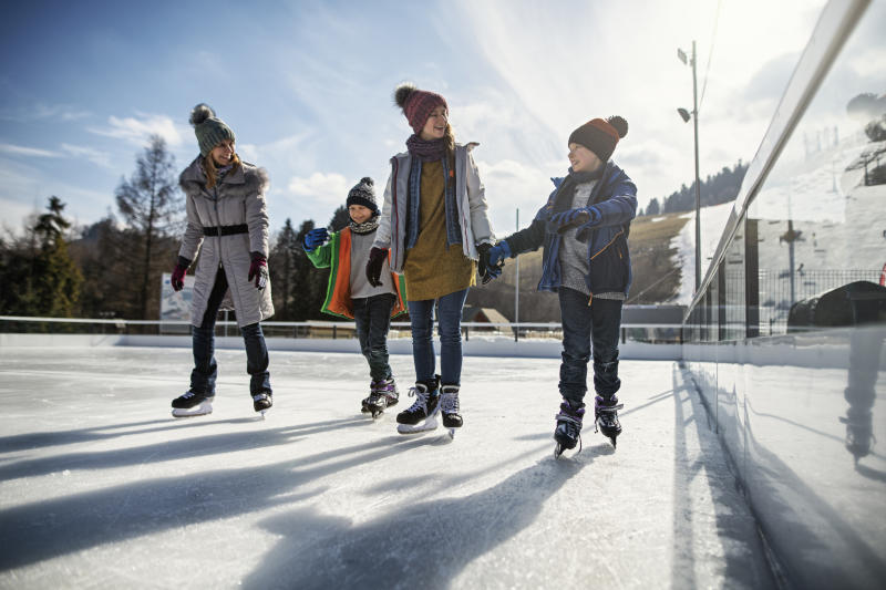 Mother and three kids spending time on ice-skating rink.