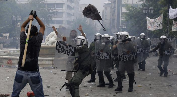A protester prepares to hit riot police with a stick during clashes at Syntagma square, central Athens, Wednesday, June 29, 2011. Greece approved more austerity measures needed to avert default next month, in a vote Wednesday that calmed markets but triggered a second day of riots that left dozens injured and the capital blanketed with tear gas.