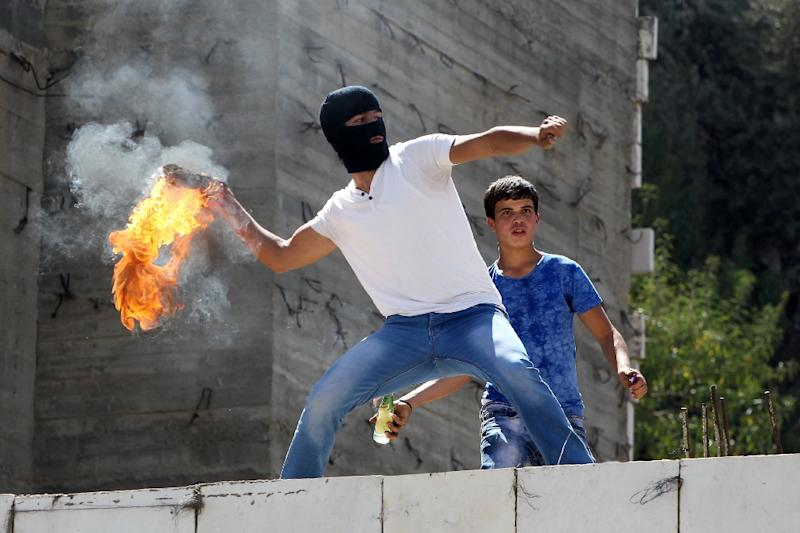 A Palestinian protester throws a petrol bomb towards Israeli security forces on September 18, 2015 in the Israel-controlled area called H2, in the West Bank town of Hebron (AFP Photo/Hazem Bader)