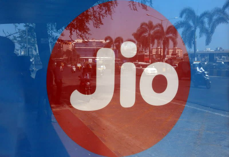 FILE PHOTO: Commuters are reflected on an advertisement of Reliance Industries' Jio telecoms unit, at a bus stop in Mumbai