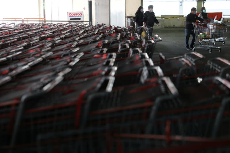 Shoppers wearing protective face masks walk past a shopping cart corral outside of a Costco store in Wheaton, Maryland