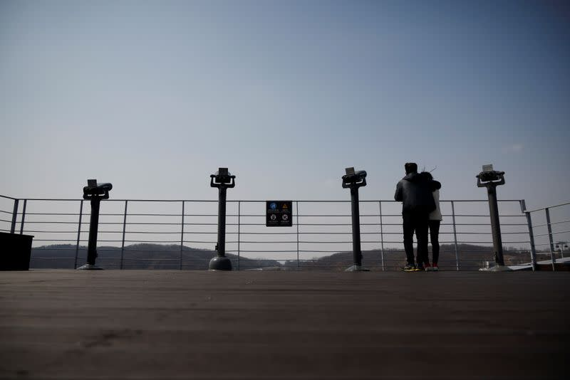 A couple looks toward the north at an observatory platform near the demilitarized zone separating the two Koreas in Paju