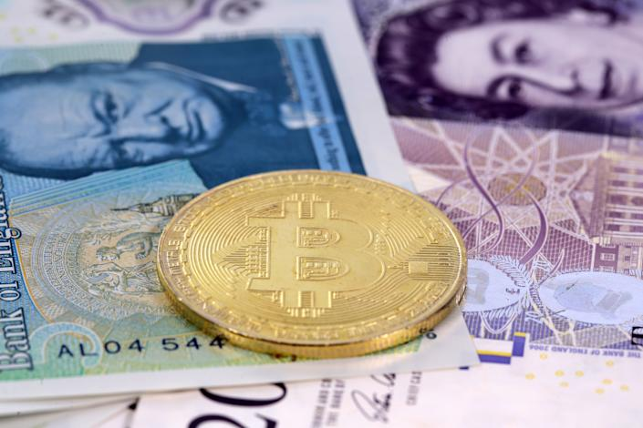 Single virtual cryptocurrency money Bitcoin golden coin on United Kingdom Pound sterling banknotes with faces of Queen Elizabeth II and Winston Churchill.
