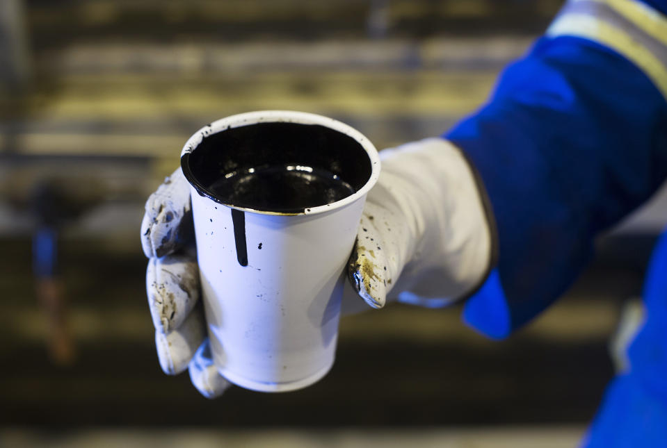 A worker holds a cup of heavy oil before it is shipped to the market at the Cenovus Energy Christina Lake Steam-Assisted Gravity Drainage (SAGD) project 120 km (74 miles) south of Fort McMurray, Alberta, August 15, 2013. Cenovus currently produces 100,000 barrels of heavy oil per day at their Christina Lake tar sands project. REUTERS/Todd Korol  (CANADA - Tags: ENERGY BUSINESS)