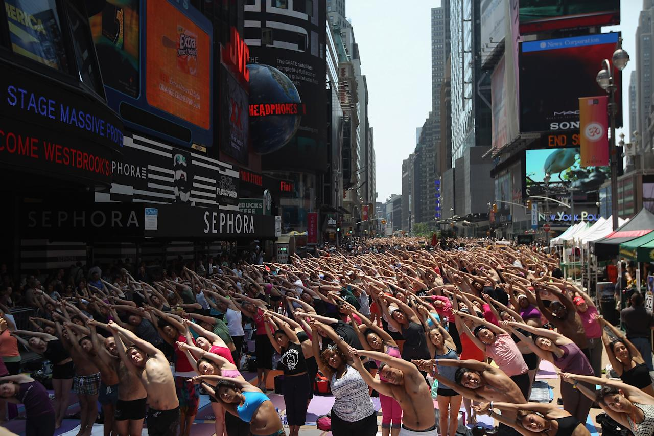 NEW YORK, NY - JUNE 20:  People brave high temperatures while practicing bikram yoga as part of the annual Mind Over Madness event in Times Square on June 20, 2012 in New York City. The event is held annually on the summer solstice, the longest day of the year and the first day of summer, amidst the hussle and bustle of Times Square, considered one of the busiest places on earth.  (Photo by John Moore/Getty Images)