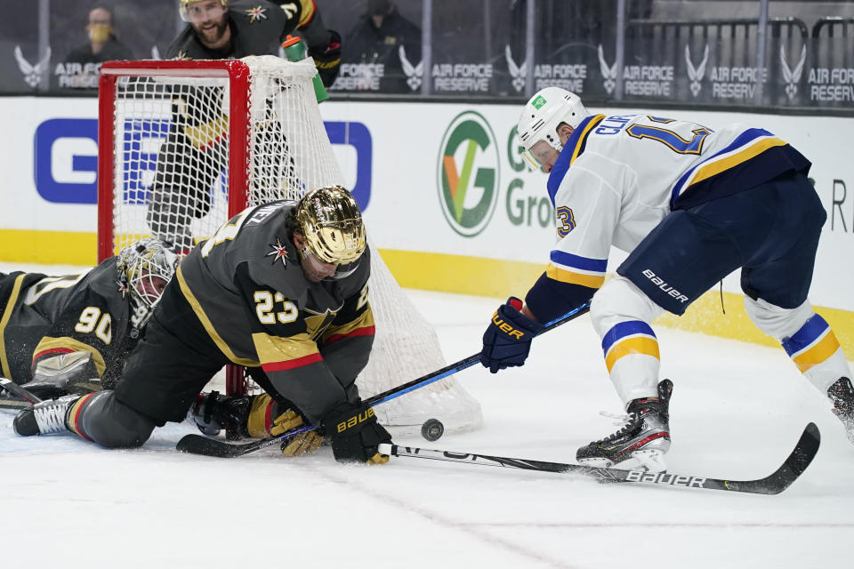 Vegas Golden Knights defenseman Alec Martinez (23) stops an attempted shot by St. Louis Blues left wing Kyle Clifford (13) during the third period of an NHL hockey game Friday, May 7, 2021, in Las Vegas. (AP Photo/John Locher)