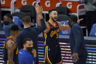 Golden State Warriors guard Stephen Curry, middle, celebrates after scoring against the Miami Heat during overtime in an NBA basketball game in San Francisco, Wednesday, Feb. 17, 2021. (AP Photo/Jeff Chiu)