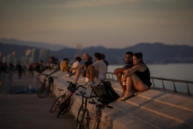 People sit on a seafront promenade during a sunset in Barcelona, Spain, enjoying their second day of outdoor exercise after lockdown restrictions were eased. (AP)