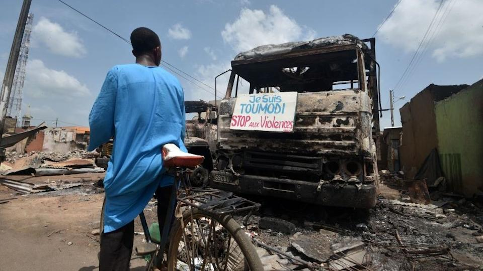 A cyclist reads a sign on a burnt truck calling for violence to stop in the market of Toumodi on November 4, 2020.