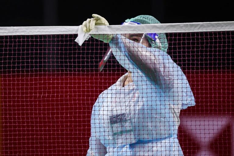 This handout from the Badminton Association of Thailand shows an official cleaning a net as a preventive measure against the spread of Covid-19