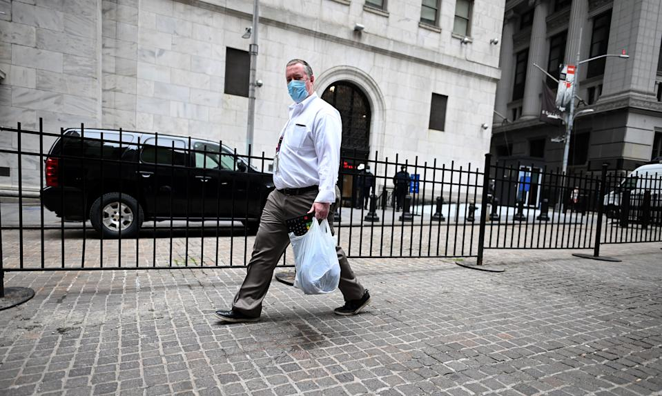A Trader wearing a mask arrives with his special keyboard before the opening bell at the New York Stock Exchange (NYSE) on May 26, 2020 on Wall Street in New York City. - Global stock markets climbed Monday, buoyed by the prospect of further easing of coronavirus lockdowns despite sharp increases in case rates in some countries such as Brazil. Over the weekend, US President Donald Trump imposed travel limits on Brazil, now the second worst affected country after the United States, reminding markets that while the coronavirus outlook is better, the crisis is far from over. (Photo by Johannes EISELE / AFP) (Photo by JOHANNES EISELE/AFP via Getty Images)