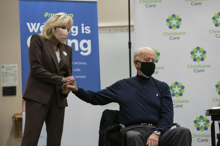 Future first lady Jill Biden holds the hand of US President-elect Joe Biden after he recieved a Covid-19 vaccination