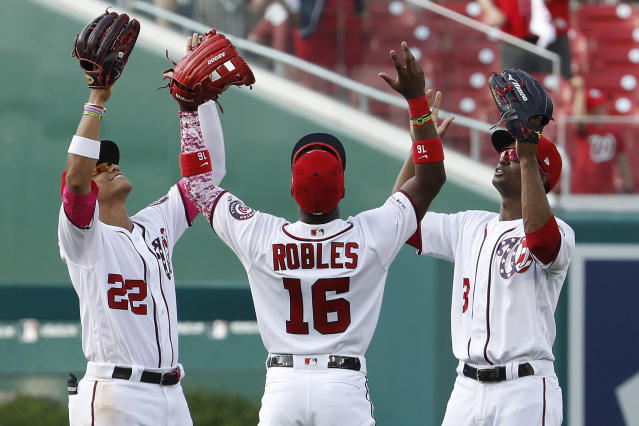 Washington Nationals left fielder Juan Soto (22), center fielder Victor Robles (16) and center fielder Michael A. Taylor (3) celebrate their win over the Miami Marlins, Sunday, May 26, 2019, in Washington. (AP Photo/Jacquelyn Martin)