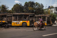 A man bikes past burnt public transport buses parked at Kyimyindaing township in Yangon, Myanmar Monday, April 12, 2021. Local news media reported that the buses got burned early Monday morning, but provided no details for the cause. (AP Photo)