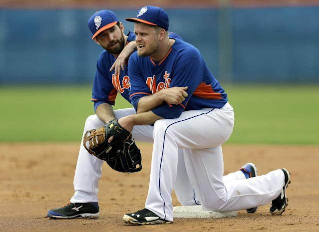 New York Mets' Ike Davis, left, and Lucas Duda kneel on first base while watching teammates participate in a fielding drill during spring training baseball practice Saturday, Feb. 22, 2014, in Port St. Lucie, Fla. (AP Photo/Jeff Roberson)