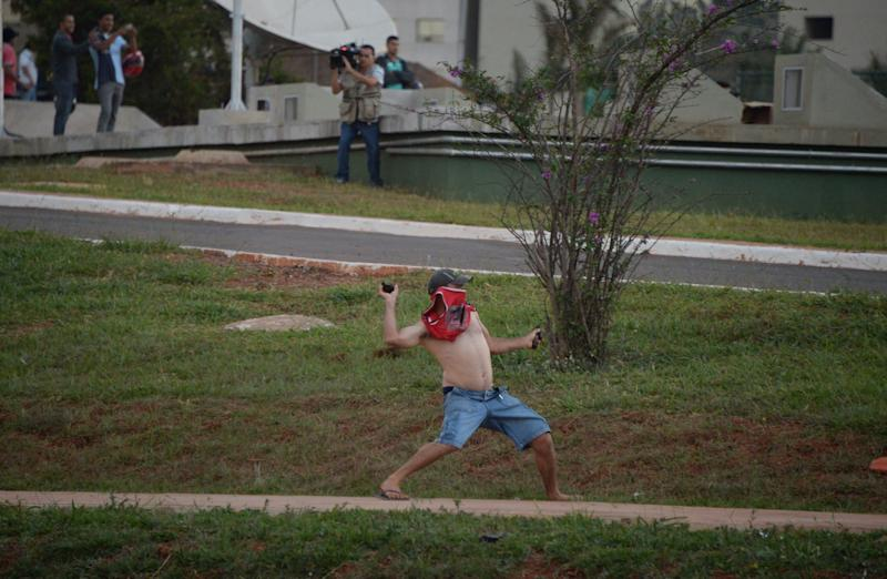 A demonstrator throws stones at riot policemen