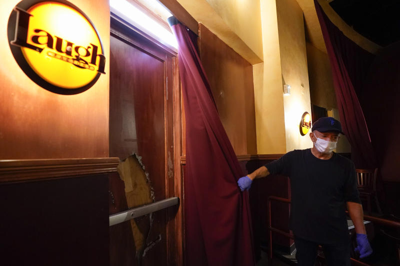 Jamie Masada shows a broken window that has been boarded at Laugh Factory on Monday, June 1, 2020, in Long Beach after overnight protests over the death of George Floyd. Floyd died in police custody on Memorial Day in Minneapolis. (AP Photo/Ashley Landis)