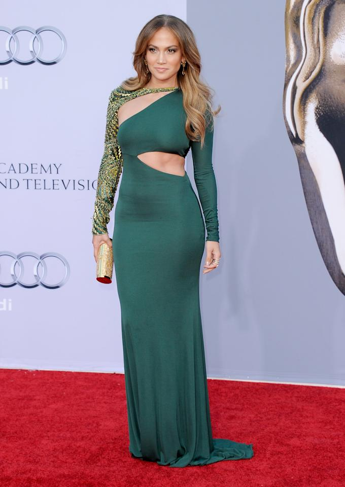 <p>Ditching the deep neckline, the performer rocked an elegant green, maxi bodycon – but still managed a brief glimpse of her well-earned abs. [Photo: Getty] </p>