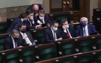 Poland's Justice Minister Zbigniew Ziobro, center, with tablet, and members of his small Solidarity Poland party that is a partner in the ruling right-wing coalition, after a crucial vote in parliament, in Warsaw, Poland, on Tuesday, May 4, 2021. Polish lawmakers have voted to approve the nation's spending plan for the 58 billion euros ($70 billion) it expects to receive from the European Union's pandemic recovery plan. (AP Photo/Czarek Sokolowski)