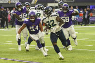 Seattle Seahawks running back Chris Carson (32) runs for a touchdown in front of Minnesota Vikings middle linebacker Eric Kendricks (54) and defensive tackle Michael Pierce (58) in the first half of an NFL football game in Minneapolis, Sunday, Sept. 26, 2021. (AP Photo/Jim Mone)