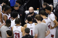 Louisville head coach Chris Mack, center, talks with his team during the first half of an NCAA college basketball game against Duke in the second round of the Atlantic Coast Conference tournament in Greensboro, N.C., Wednesday, March 10, 2021. (AP Photo/Gerry Broome)