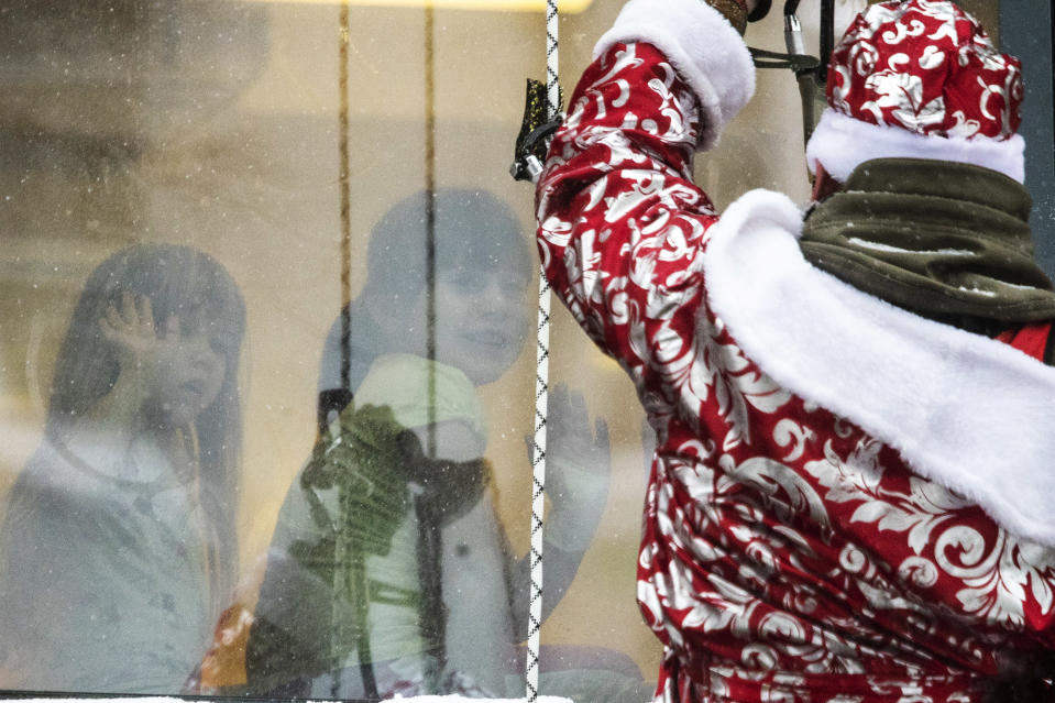 A Russian emergency rescue worker dressed as Ded Moroz (Santa Claus, or Father Frost) greets children as he scales the wall of a children hospital to mark the upcoming New Year celebrations, Russia, Friday, Dec. 25, 2020. Russia, which has so far registered more than 2.9 million confirmed cases of the virus and over 52,000 deaths in the pandemic, has been swept by a rapid resurgence of the outbreak this fall, with numbers of infections and deaths significantly exceeding those reported in the spring. Usually, performers come into children's rooms, but this year because of the virus-related restrictions, the artists had to perform outside of the hospital at a significant distance. (AP Photo/Pavel Golovkin)