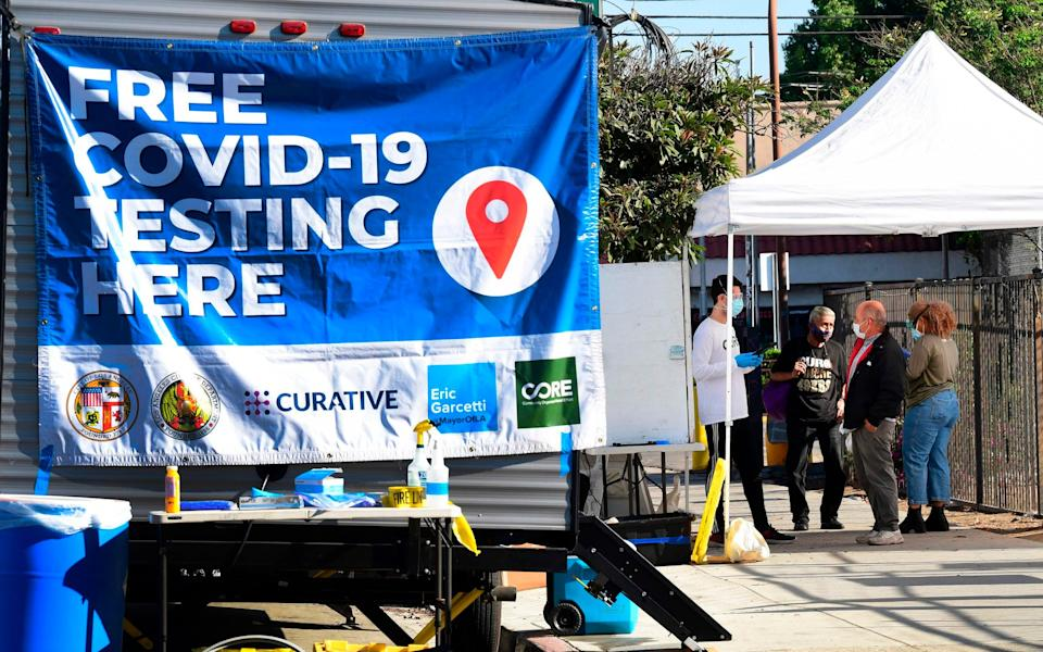 People check-in at a pop-up Covid-19 Test site in Los Angeles, California - FREDERIC J. BROWN / AFP