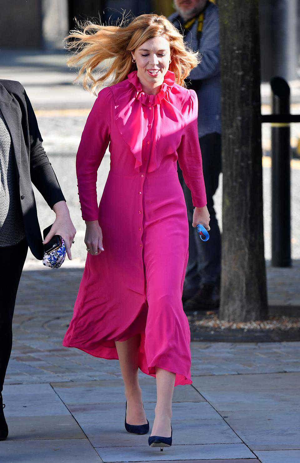 Carrie Symonds stood out from the crowd in a bright fuchsia £85 dress from & Other Stories on day four of the Conservative Party Conference in Manchester [Photo: Getty Images