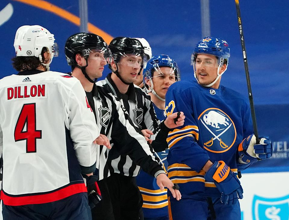 BUFFALO, NY - APRIL 9: The linesman separate Brenden Dillon #4 of the Washington Capitals and Brandon Montour #62 of the Buffalo Sabres during the third period at KeyBank Center on April 9, 2021 in Buffalo, New York. (Photo by Kevin Hoffman/Getty Images)