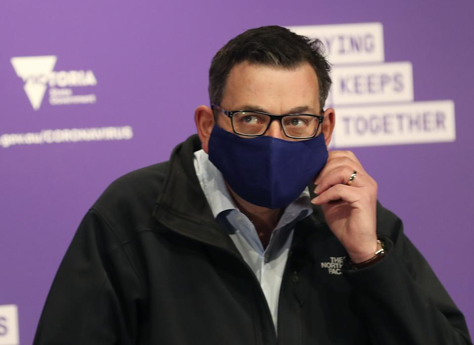 Victorian Premier Daniel Andrews arrives in a face mask to speak to the media during a press conference in Melbourne.