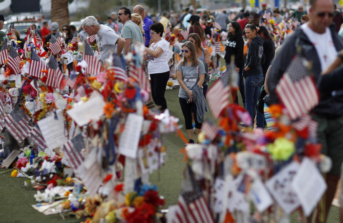 """FILE - In this Nov. 12, 2017, file photo, people visit a makeshift memorial honoring the victims of the Oct. 1 mass shooting in Las Vegas. A public panel planning a permanent Las Vegas memorial honoring victims of the deadliest mass shooting in modern U.S. history heard that there's no perfect answer to how a tribute should look and feel. """"The goal is to provide comfort and hope and facilitate healing,"""" Anita Ahuja, manager of mass violence response for the California Victim Compensation Board, advised the 1 October Memorial Committee during its initial meeting Nov. 25, 2020. (AP Photo/John Locher, File)"""