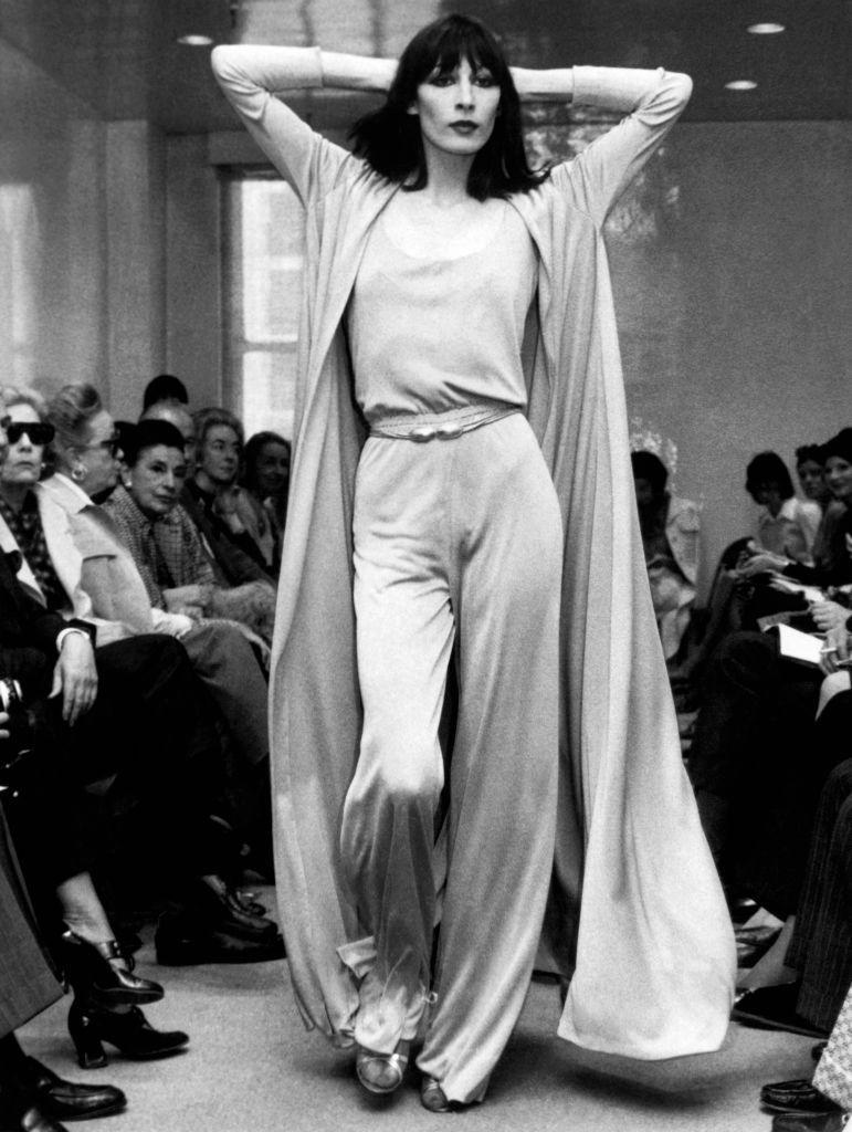 <p>Halston's designs became hugely popular among celebrities, and his shows were can't-miss, who's-who events. Angelica Huston is shown here modeling a Halston original at one of his shows.</p>
